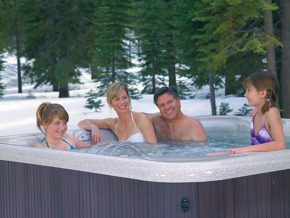 hot tubs all year round - family in hot tub winter image